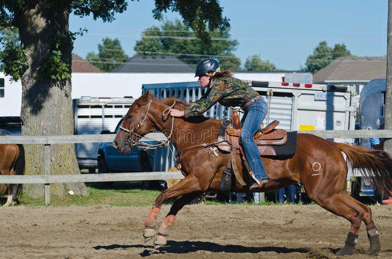Young teen cowgirl at country fair racing horse. Young teenage girl racing horse in competition at country fair royalty free stock image