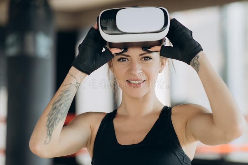 Young teen gamer wearing augmented reality glasses standing in boxing stance playing action simulator game mobile app royalty free stock photography