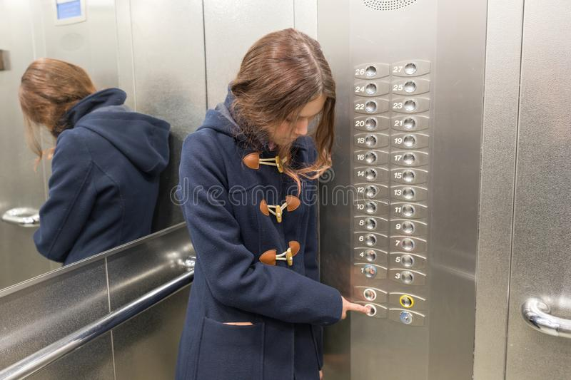 Young teen girl in elevator, presses the elevator button stock image