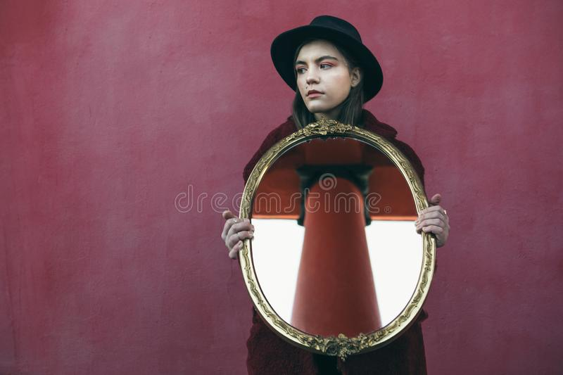 Young teen girl in hat holding mirror in front of red wall. the mirror reflects the column of the building opposite. Opinion of society. Conceptual creative royalty free stock photo