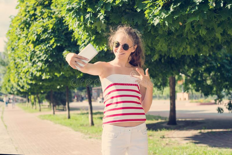 Young teen girl having fun with the phone, takes a video, takes a selfie royalty free stock photography