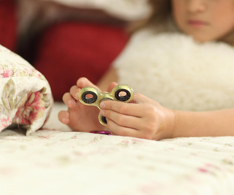Young teen girl holding popular fidget spinner toy - closeup shot. at home on bed stock images