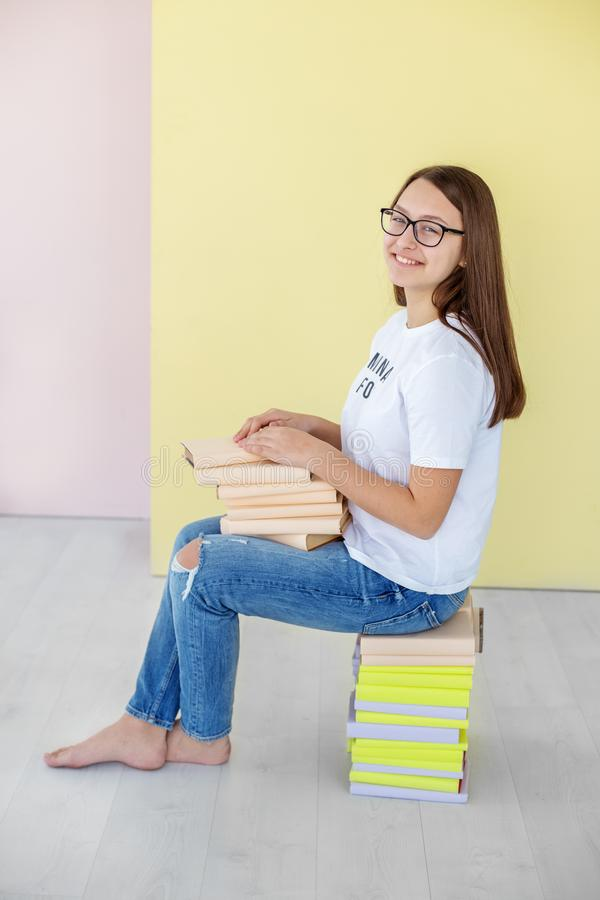 A young teen girl holds a lot of books. Happy laughing girl. Concept of education, hobby, study and world royalty free stock images