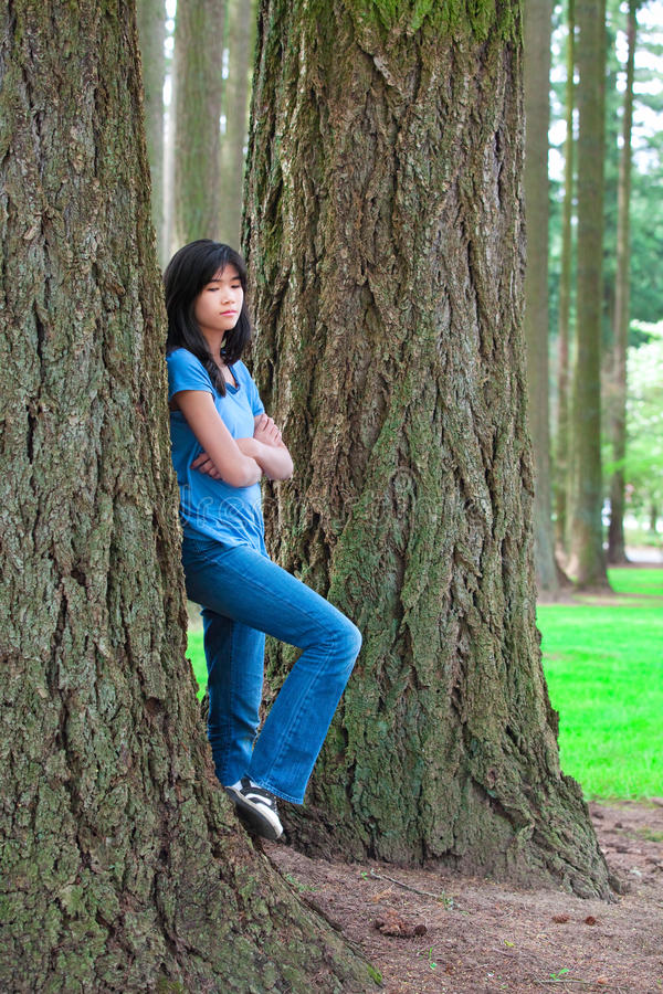 Young teen girl leaning against large pine tree trunk, sad stock photos