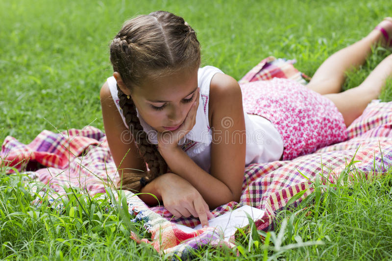 Young teen girl lying on green grass and reading book royalty free stock images