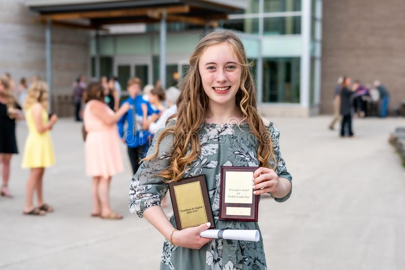 Young Teen Girl/Middle School student standing in front of school with awards and diploma after Grade 8/Middle school graduation c royalty free stock photo