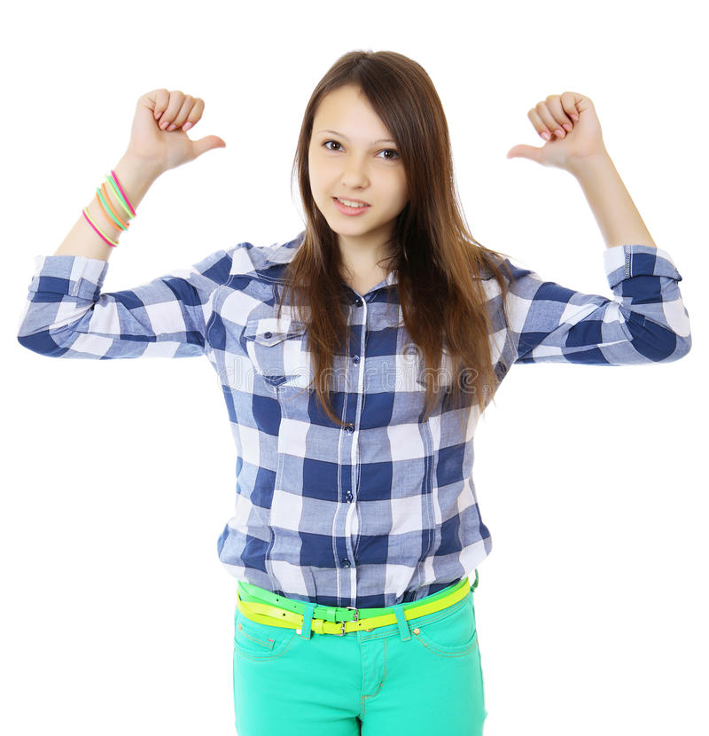 Young teen girl pointing behind with her thumb. Young woman in a plaid shirt points a two finger behind his back. stock photos