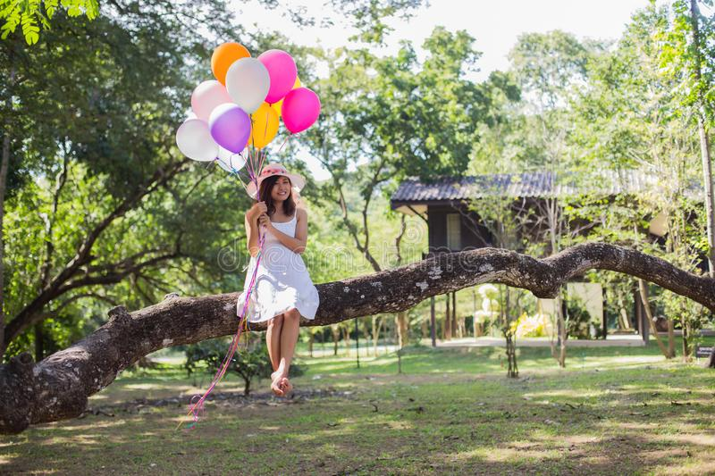 Young teen girl sitting on tree and holding balloons in hand royalty free stock images