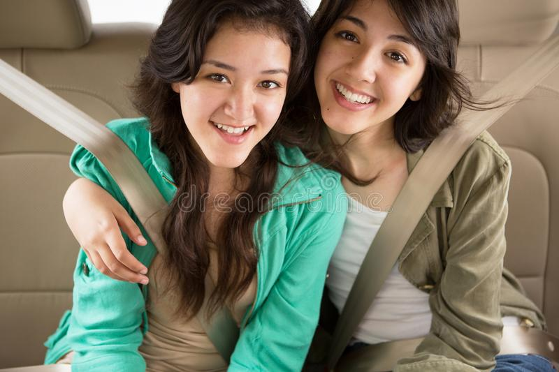 Young teen girls smiling in the backseat royalty free stock photos