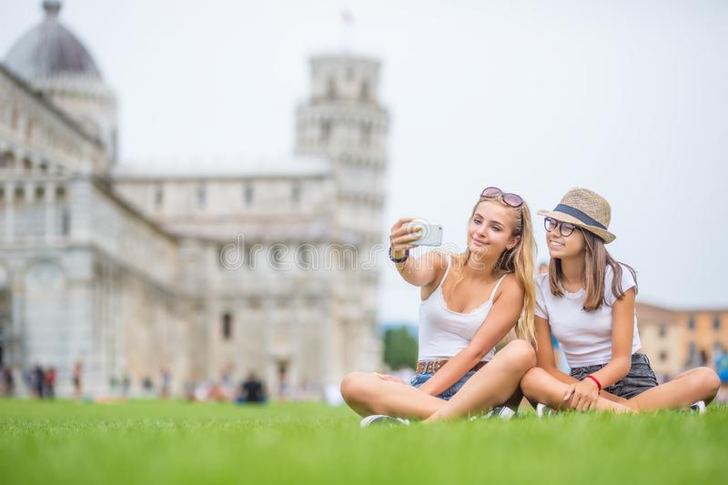 Young teen girls traveler tourist before Pisa tower selfie for smartphone picture or video. Italy, leaning, happy, europe, vacation, holiday, summer, photo stock image