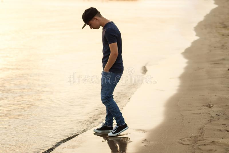 Young teen watching the water on beach in the evening light.  stock images