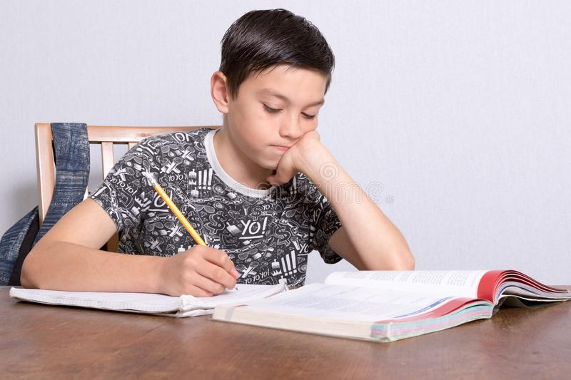 Young teenage boy doing his homework. At home stock photography