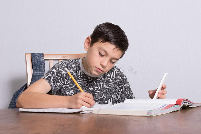 Young teenage boy doing his homework. And using his phone stock images