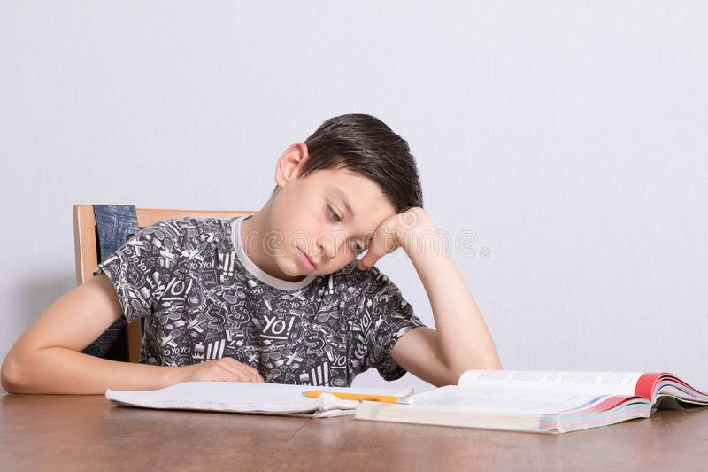 Young teenage boy doing his homework. At home royalty free stock photos