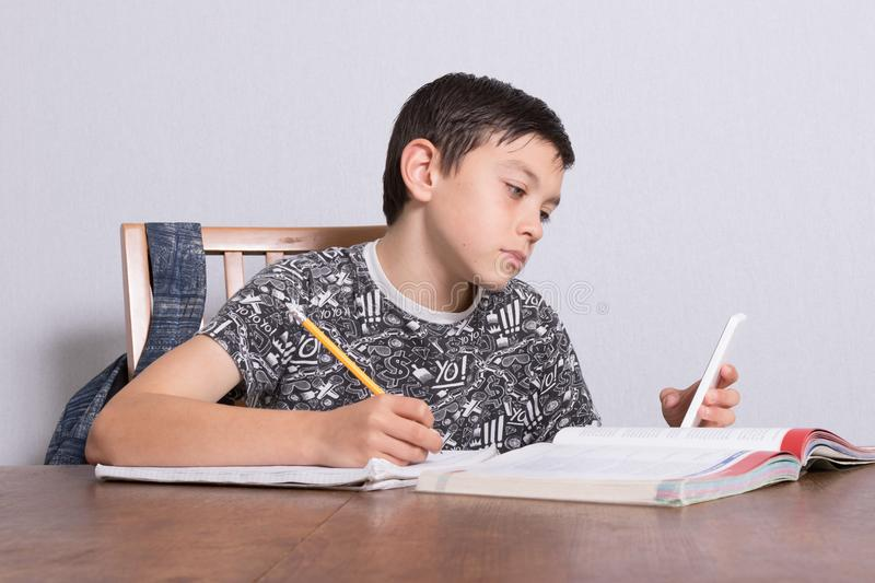 Young teenage boy doing his homework. And using his phone royalty free stock images