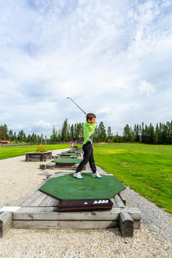 Young teenage boy outdoors at a driving range playing golf and practice his swing. royalty free stock photography