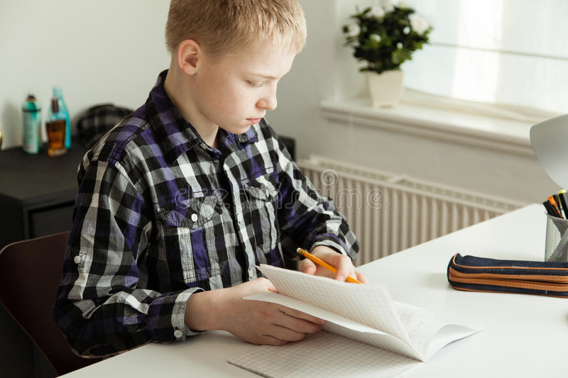 Young Teenage Boy Sitting at Desk Doing Homework stock photography