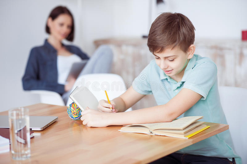 Young teenage boy studying at desk stock photos