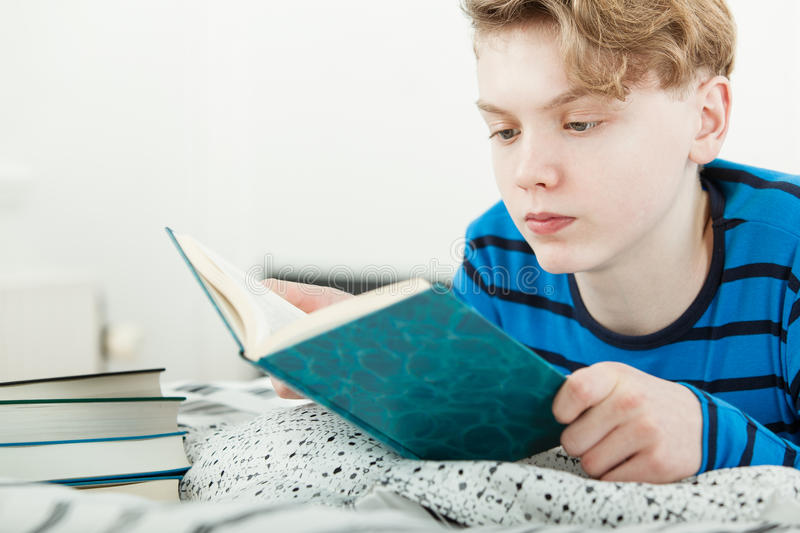 Young teenage boy studying at home on his bed royalty free stock photo