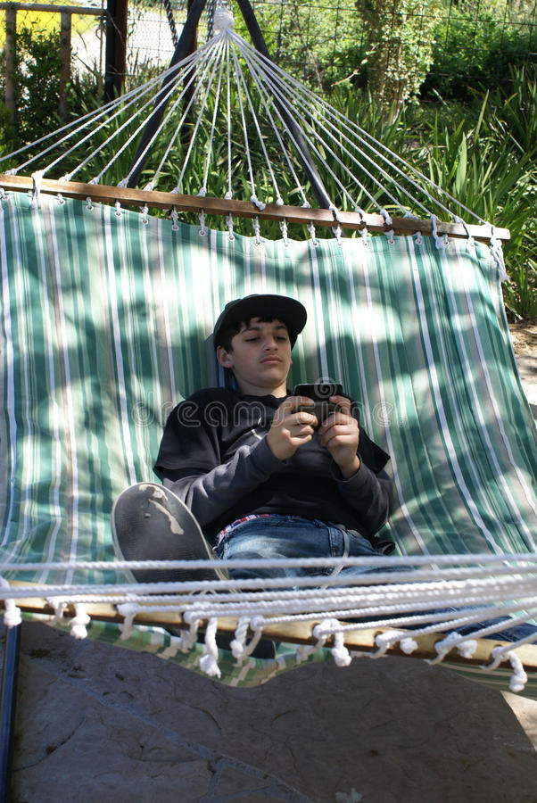 Young Teenage Boy Texting on Phone stock images