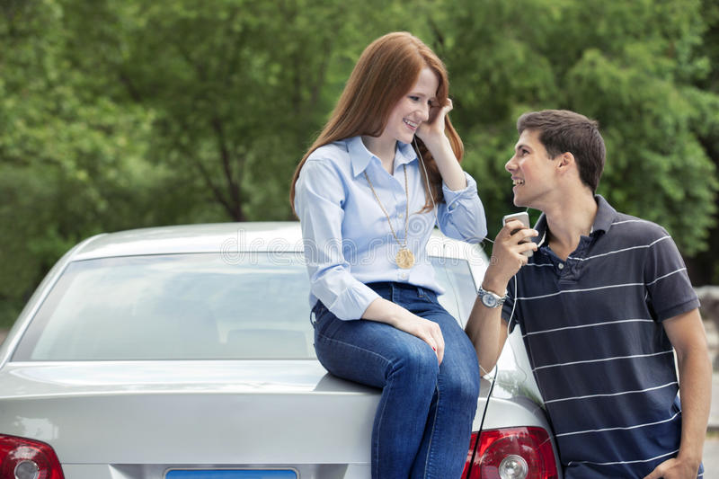 Young teenage drivers with car. Teenagers with car in park royalty free stock image