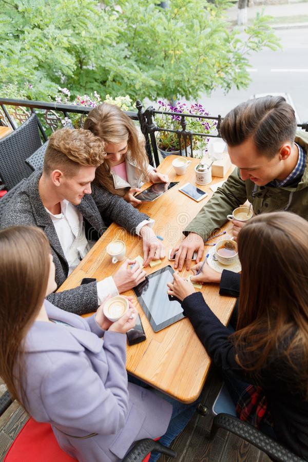 Young cheerful friends chatting at the cafe on the outdoors background. Friendship concept. stock images