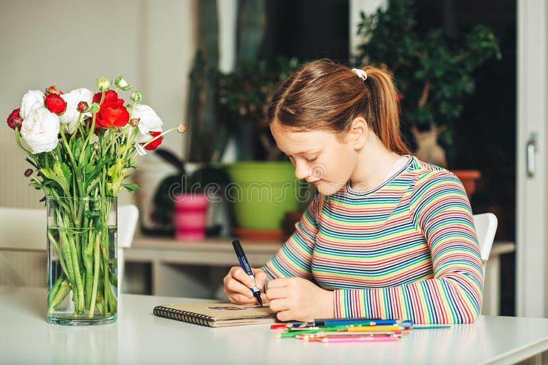 Young teenage girl drawing at home stock photo