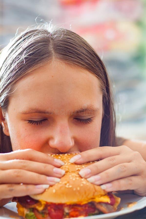 Young teenage girl eat burger. Girl trying to eat fast food. Portrait of young teenage girl eat burger. Girl trying to eat fast food royalty free stock photo