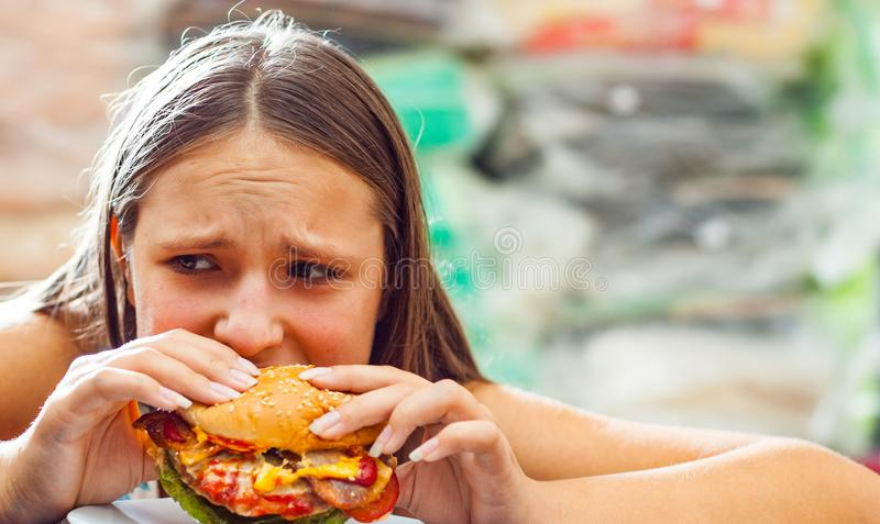 Young teenage girl eat burger. Girl trying to eat fast food. Portrait of young teenage girl eat burger. Girl trying to eat fast food stock photos