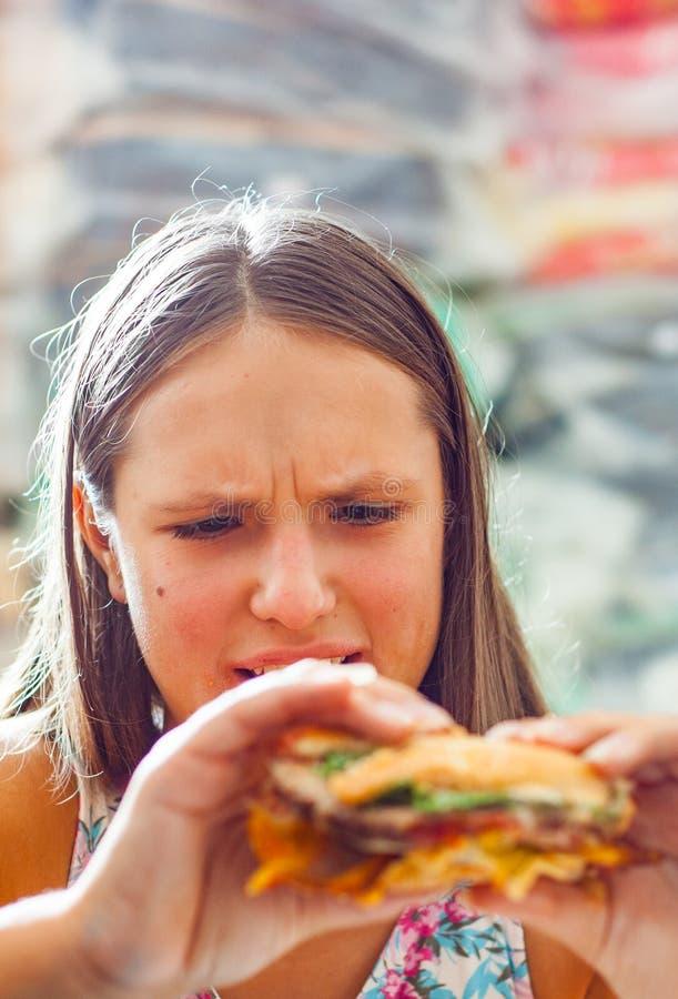 Young teenage girl eat burger. Girl trying to eat fast food. Portrait of young teenage girl eat burger. Girl trying to eat fast food royalty free stock image