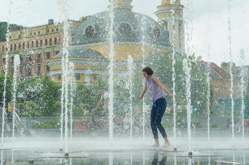 Young teenage girl in fountain. Girl happy, clothes wet, background city architecture. stock photo
