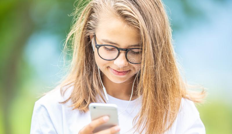 Young teenage girl with headphones enjoying with good music. Modern young woman with cellphone royalty free stock photo