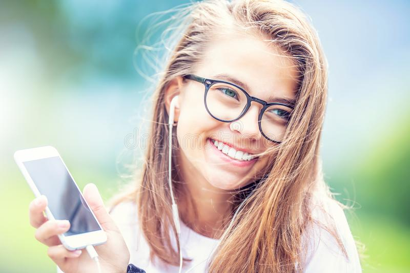 Young teenage girl with headphones enjoying with good music. Modern young woman with cellphone stock photography