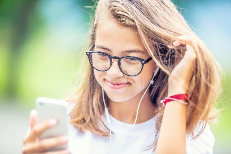 Young teenage girl with headphones enjoying with good music. Modern young woman with cellphone stock images