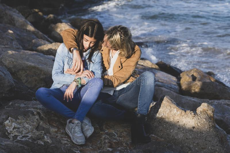 Young teenage girl with her mother in affectionate gesture by the sea. Family vacations on the coast royalty free stock photos