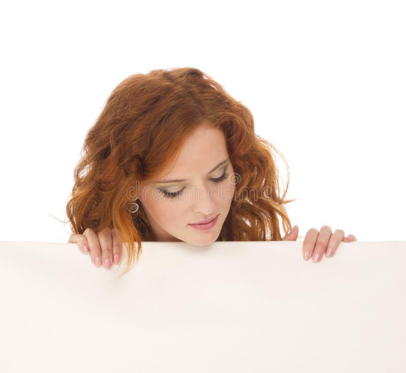 Young teenage girl hiding behind a billboard