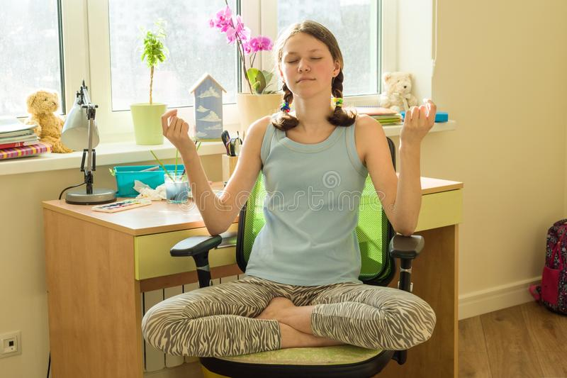 Young teenage girl meditates at home on a chair near the window table, in lotus pose stock image