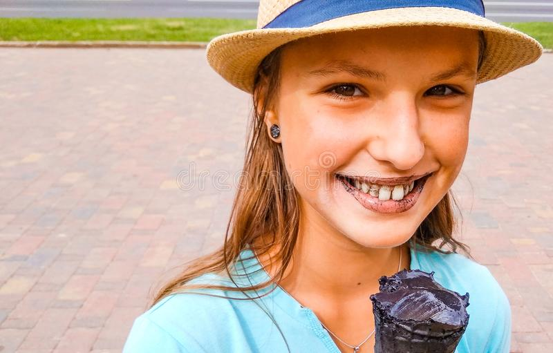 Young teenage girl outdoors eating black ice cream cone on the city stock photo