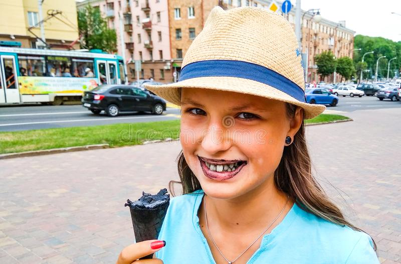 Young teenage girl outdoors eating black ice cream cone on the city stock image