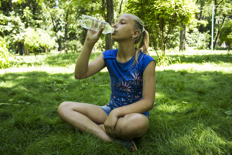 Young teenage girl in a park drinking water royalty free stock image