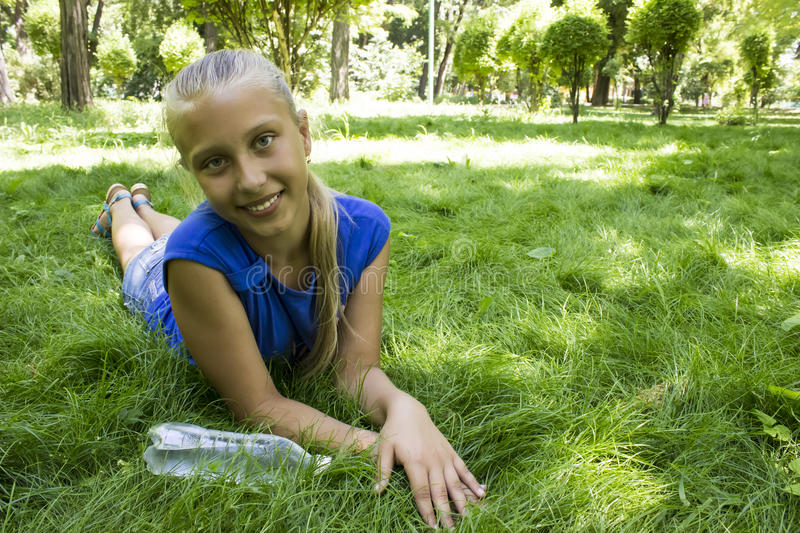 Young teenage girl in a park lying on the green meadow royalty free stock photography