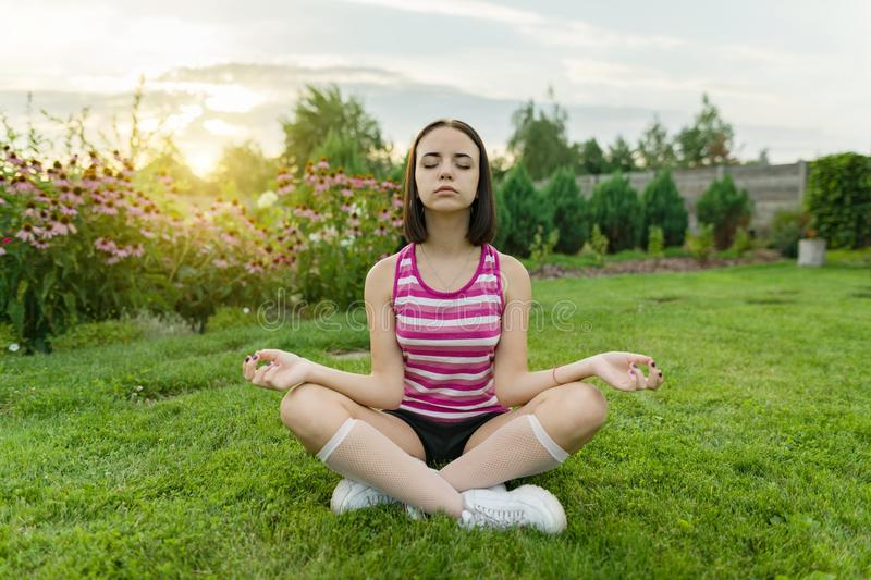 Young teenage girl practicing yoga, meditating on a summer sunset background, on green grass, lawn near the house. Young teenage girl practicing yoga royalty free stock photos