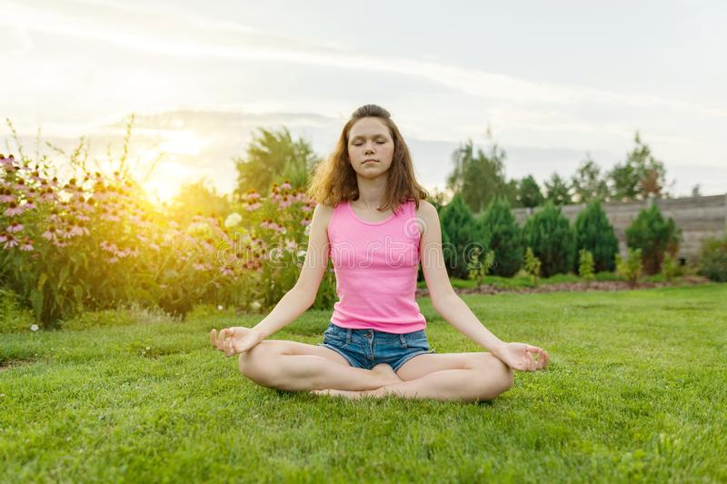 Young teenage girl practicing yoga, meditating on a summer sunset background, on green grass, lawn near the house. stock images