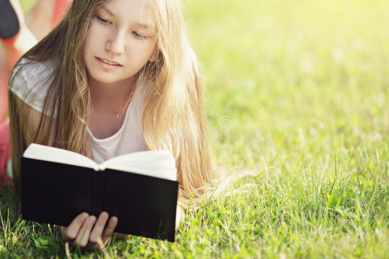 Young teenage girl reading book on grass royalty free stock images