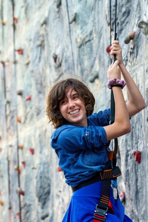 Young Teenage Girl Repelling Down From a Rock Wall Turns To Smile At Friends stock photography