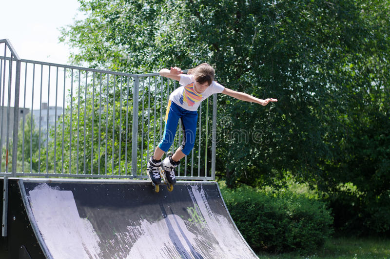 Young teenage girl roller blading. Active energetic young teenage girl roller blading launching herself from the top of a cement ramp in a skate park royalty free stock photography