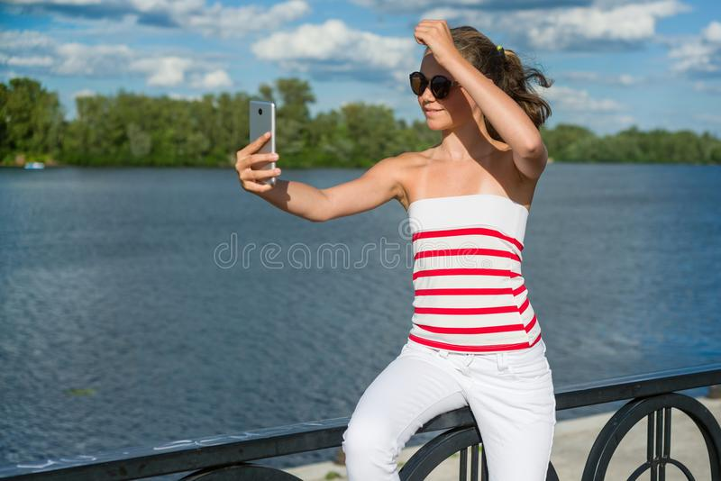 A young teenage girl shoots video on a smartphone for her channe stock photo