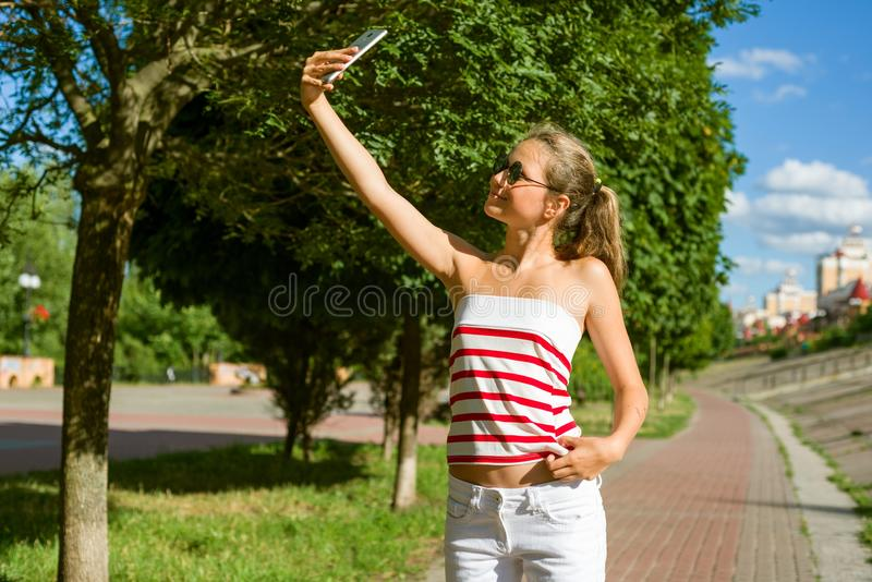 A young teenage girl shoots video on a smartphone for her channe. L in YouTube. On a sunny summer day, in the city park royalty free stock image