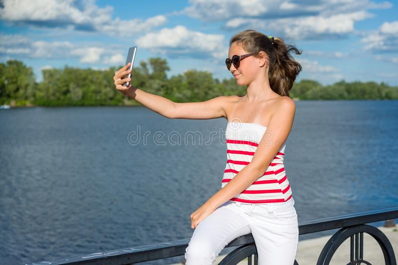 Young teenage girl shoots video on a smartphone stock photography