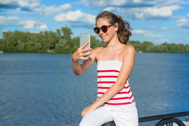 A young teenage girl shoots video on a smartphone for her channel . royalty free stock photo